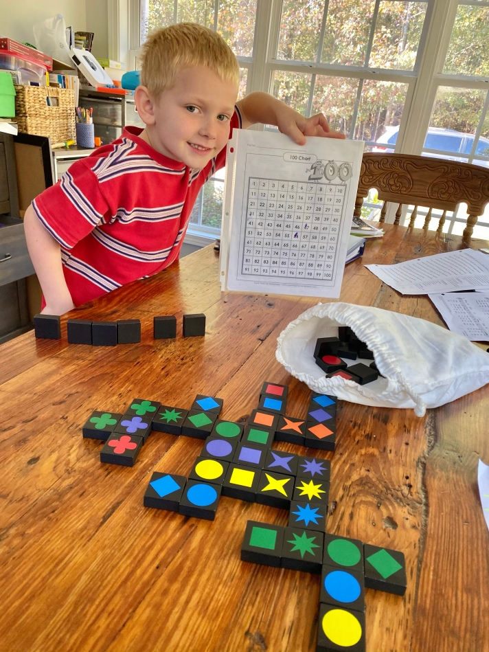 Boy using a hundreds chart to help to play the game Qwirkle