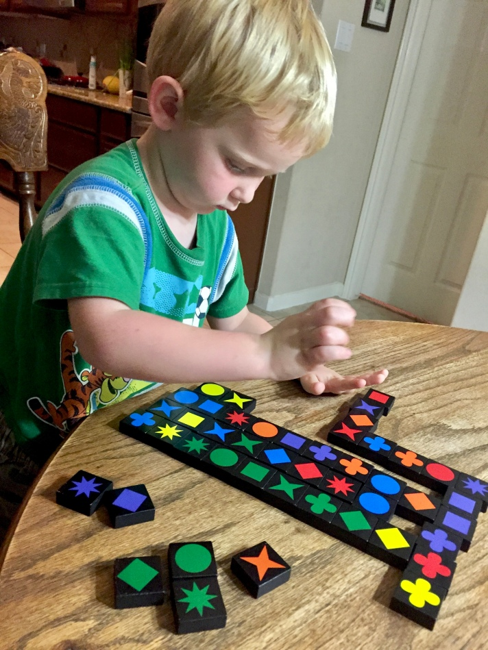 Little boy playing colorful tile game